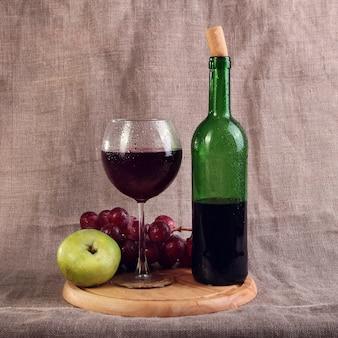 Czerwone wino, sery i winogrona w układzie martwej natury.