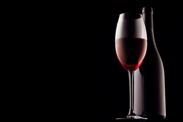 Czerwone wino, szkło i butelka na czarnym tle, zbliżenie miejsca kopiowania.