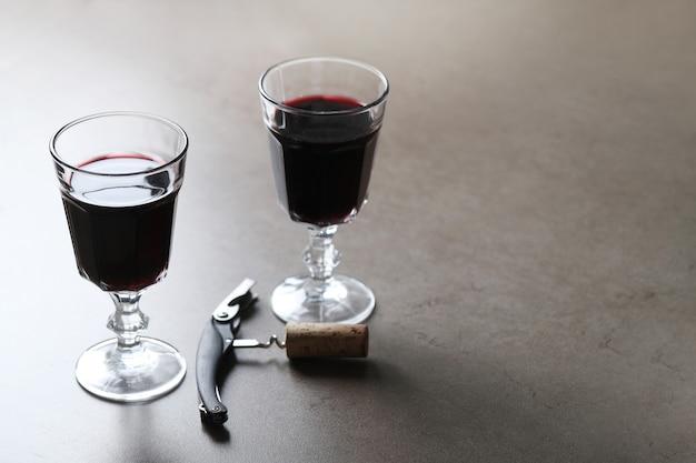 Czerwone wino w kieliszkach i korkociągu