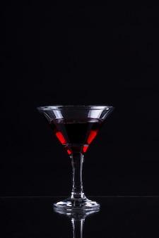 Czerwone wino w kieliszku martini na czarnym tle