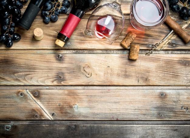 Czerwone wino w kieliszku z winogronami i korkociągiem na drewnianym stole.