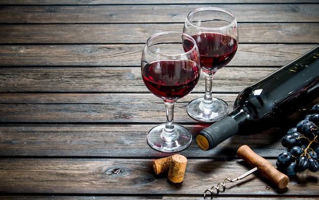 Czerwone wino w okularach z winogronami na drewnianym stole.