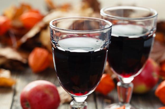 Czerwone wino w szkłach na stole w spadku leaf