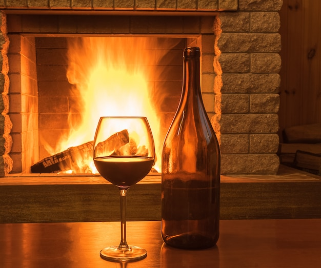 Czerwone wino w szklance i butelce, przed przytulnym kominkiem, w wiejskim domu, zimą.