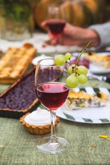 Czerwone wino w szklance na świątecznym stole w ogrodzie.