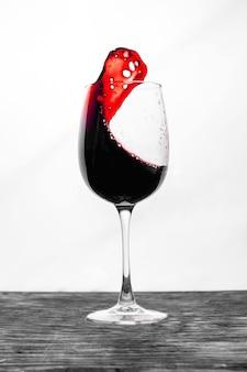 Czerwone wino w szklance rozpryskuje się w ruchu