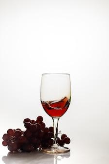 Czerwone wino w szkle z czerwonych winogron na białej powierzchni.