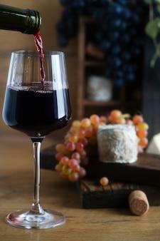 Czerwone wino wlewa się do kieliszka, obok koziego sera i winogron. zdjęcie wysokiej jakości