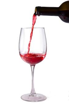 Czerwone wino wlewa się do kieliszka z butelki, izoluje na białym tle