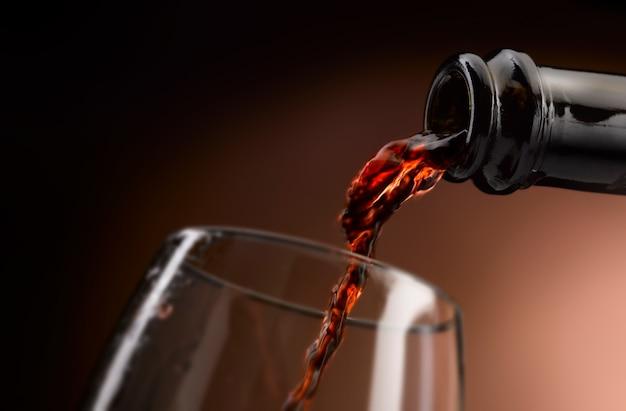 Czerwone wino wlewa się do kieliszka