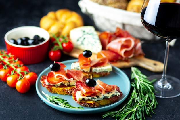 Czerwone wino wlewa się do sera dzwonowego, jamon, prosciutto i oliwek na czarnym tle. wino przekąska na drewnianej desce. chleb z serem i przekąskami do wina. pyszne przekąski na imprezę.