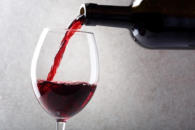 Czerwone wino wlewa się do szklanki z butelki.