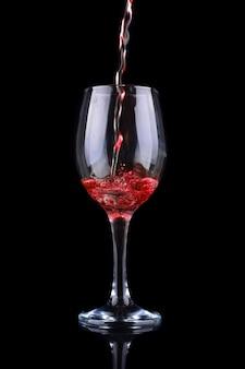 Czerwone wino wlewając do kieliszka. na białym tle na czarnym tle