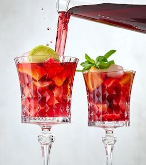 Czerwone wino wlewając do szklanki pokrojonych owoców. proces robienia czerwonej sangrii