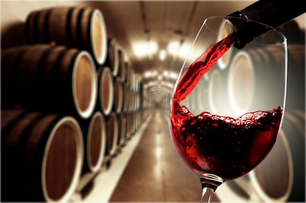 Czerwone wino wlewane do kieliszka na tle