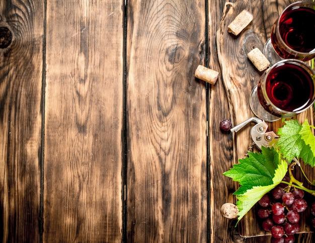 Czerwone wino z gałązką winorośli. na drewnianym stole.