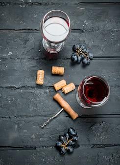 Czerwone wino z korkociągiem. na czarnym rustykalnym stole.