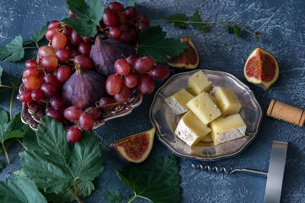 Czerwone winogrona, figi, ser, korkociąg i korek z wina i wokół winorośli