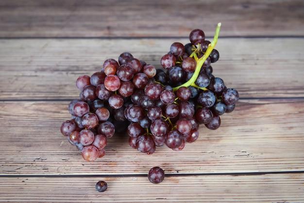 Czerwone winogrona na drewnianym stole kiść winogron soczystych owoców