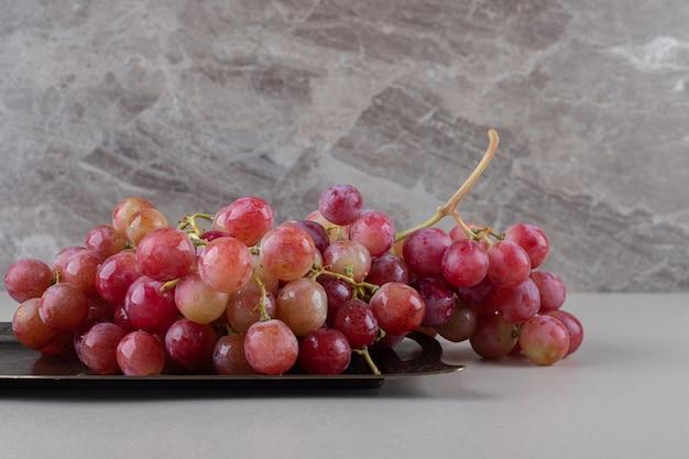 Czerwone winogrona na małej tacy na marmurze