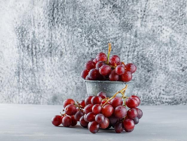 Czerwone winogrona w mini wiadrze na tynku i nieczysty.