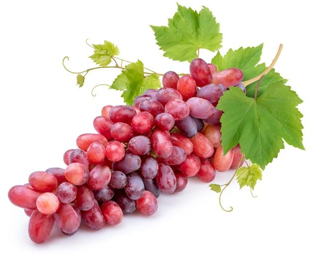 Czerwone winogrona z liśćmi na białym tle.
