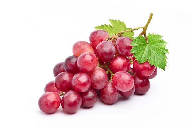 Czerwone winogrona z liśćmi na białym tle