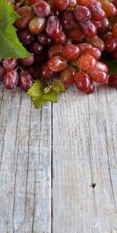 Czerwone winogrona z liśćmi na starym drewnianym stole z bliska