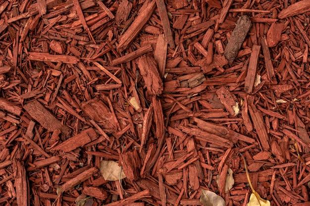 Czerwone wióry z kory drzewa na ziemi obraz w tle