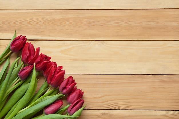 Czerwone wiosenne kwiaty tulipanów na drewnianym stole. kwitnące płatki wiosny. piękne czerwone tulipany na wiosnę. tulipanowy kwiat z zielonymi listkami na drewnianym tle. dzień wiosny na pocztówkę