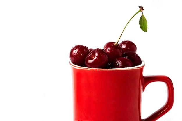 Czerwone wiśnie w filiżance na białym tle