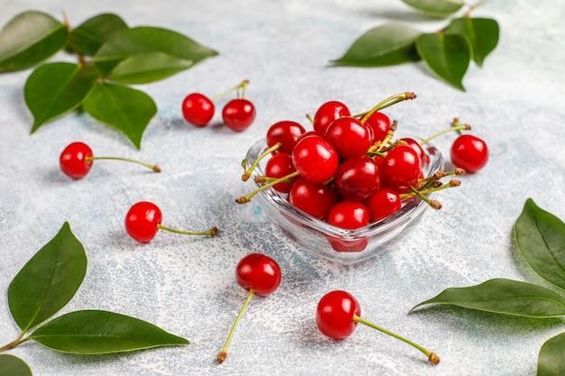 Czerwone wiśnie w przezroczystej szklanej misce na szarym stole
