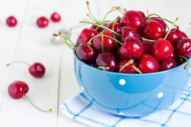 Czerwone wiśnie w pucharze na białym drewnie na błękitnym ręczniku