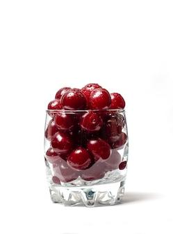 Czerwone wiśnie w szklanej filiżance na białym tle