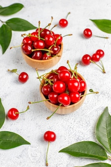 Czerwone wiśnie w talerzu rzucają kulą na popielatym stole