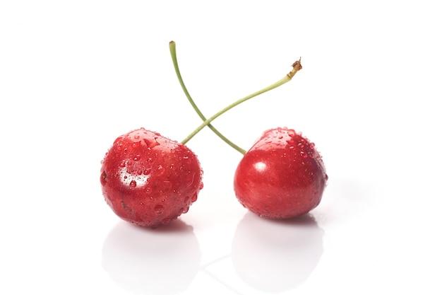 Czerwone wiśnie z kroplami wody, zbliżenie. na białym tle.