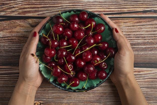 Czerwone wiśnie z zielonymi łodygami w ozdobnym talerzu