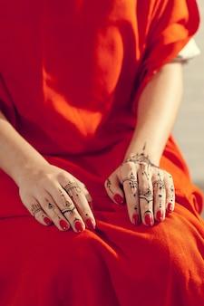 Czerwone, wypielęgnowane dłonie z mehndi
