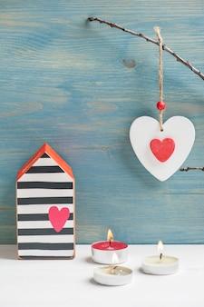 Czerwone wytarte drewniane serce, zapalone świece