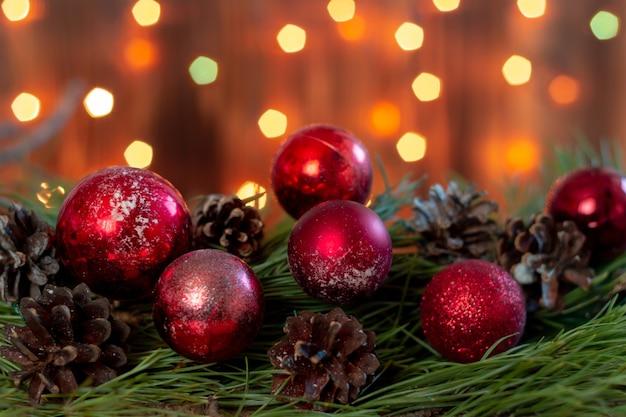 Czerwone zabawki kulki i stożki na gałęzi choinki na tle rozmytych świateł bokeh