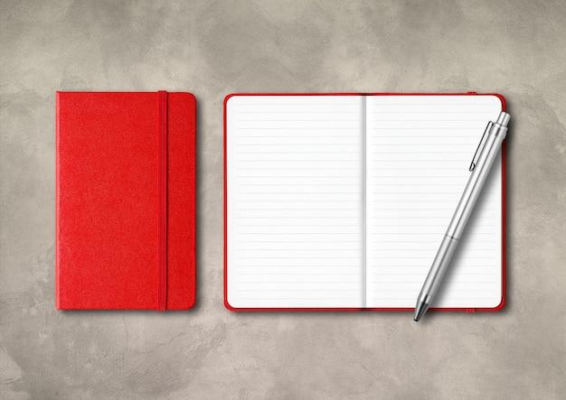 Czerwone, zamknięte i otwarte zeszyty w linie z długopisem. makieta na białym tle na tle betonu