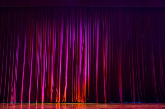 Czerwone zasłony ze światłami show i parkietem z drewna.