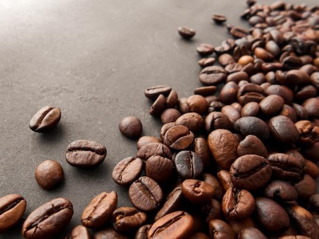 Czerwone ziarna kawy i palonych ziaren kawy samodzielnie na czarnym tle.