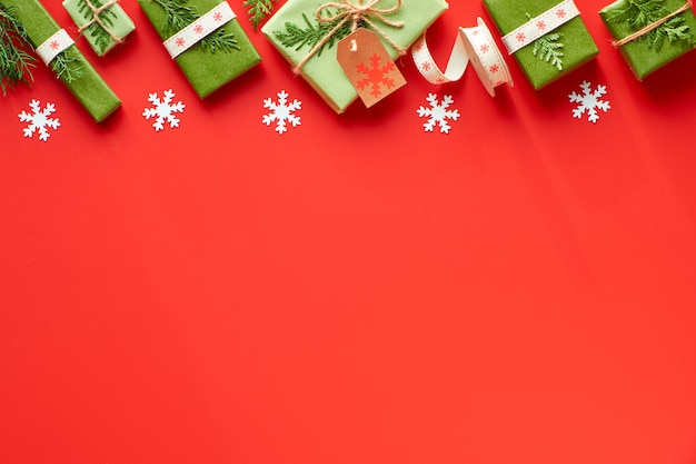 Czerwone, zielone i białe boże narodzenie. modne, przyjazne dla środowiska prezenty na boże narodzenie lub nowy rok bez odpadów. leżał płasko z ręcznie pakowanymi papierowymi pudełkami przewiązanymi sznurkiem lub bawełnianą opaską z zielonymi liśćmi, miejsce do kopiowania.