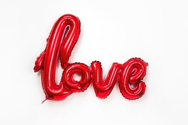 Czerwone złote słowo miłość z nadmuchiwanych balonów na białym tle