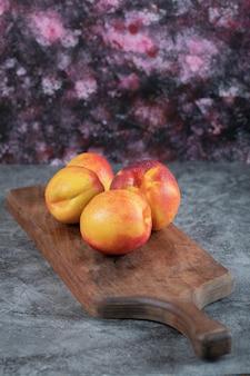 Czerwone żółte brzoskwinie na białym tle na drewnianym talerzu.