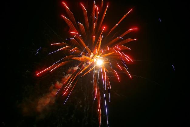 Czerwone, żółte i niebieskie fajerwerki rozprzestrzeniają się wokół musującego