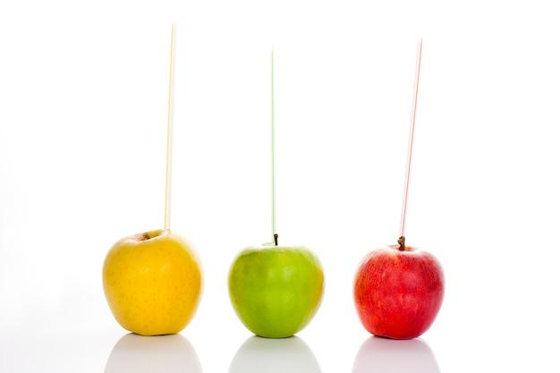 Czerwone, żółte i zielone jabłka ze słomkami na białym tle