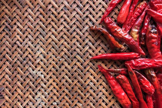 Czerwonego chili pieprz na bambusie wyplata teksturę z miękką ostrością i nadmiernym światłem w tle