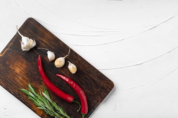 Czerwonego chili pieprze i inne pikantność na białym textured tle, odgórny widok